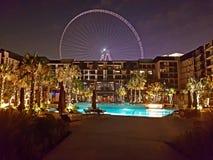 L'image de l'hôtel de Dubaï Caesar Palace du côté de piscine avec les ferris de Bluewaters roulent dedans le fond Fond de concept photographie stock libre de droits