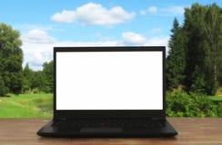 L'image de l'extérieur avec l'ordinateur portable ouvert et vident l'écran blanc pour l'espace de copie Photos stock