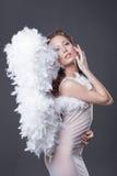 L'image de la belle femme posant avec l'ange s'envole Photos stock