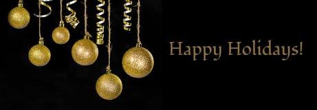 L'image de la décoration de fête de boule d'or d'arbre de Noël devant le fond noir là est le texte bonnes fêtes Photos stock