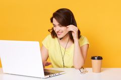 L'image de la femme de brune dans le T-shirt occasionnel jaune se repose sur la chaise au deskand blanc travaillant sur l'ordinat image stock