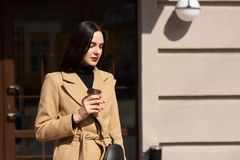 L'image de la femme magnifique de brune avec de longs cheveux, manteau de port et sac à main noir, a la manucure rouge lumineuse, photo stock