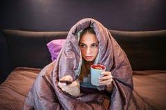 L'image de la jeune femme a couvert de couverture épaisse et regarde la TV Elle juge à télécommande dans une main et tasse de thé photographie stock