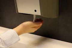 L'image de la main emploie un distributeur détersif liquide d'une boîte automatique image libre de droits