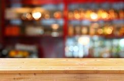 L'image de la table en bois devant le résumé a brouillé le fond des lumières de restaurant Images stock
