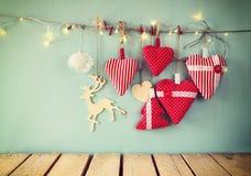 L'image de Noël des coeurs et de la guirlande rouges de tissu s'allume, accrochant sur la corde devant le fond en bois bleu Rétro Images libres de droits