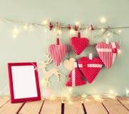 L'image de Noël des coeurs rouges de tissu et le cadre vide, guirlande s'allume, accrochant sur la corde devant le fond en bois b Image stock