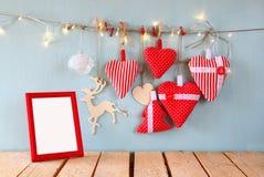 L'image de Noël des coeurs rouges de tissu et le cadre vide, guirlande s'allume, accrochant sur la corde devant le fond en bois b Photos stock
