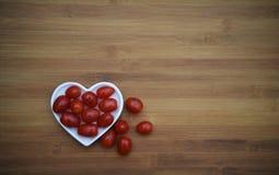 L'image de nourriture des tomates et d'une de prune rouges mûres a un tiré sur le sourire et placé avec un plat blanc de forme de Photo libre de droits
