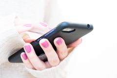 L'image de plan rapproché d'un ` s de femme remet se tenir et employer au téléphone intelligent Lumière molle, foyer sélectif images stock
