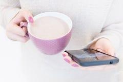 L'image de plan rapproché d'un ` s de femme remet se tenir et employer au téléphone intelligent Lumière molle, foyer sélectif photos stock