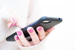 L'image de plan rapproché d'un ` s de femme remet se tenir et employer au téléphone intelligent Lumière molle, foyer sélectif photographie stock libre de droits