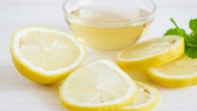 L'image de plan rapproché du citron découpe le mensonge en tranches sur le bureau blanc en bois à côté de la cuvette avec du miel Photos stock