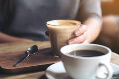 L'image de plan rapproché du ` s de tasse et de femme de café d'Americano remettent tenir la tasse de café de latte sur la table  Photographie stock libre de droits