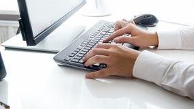 L'image de plan rapproché de la femme remet le travail sur le PC au bureau moderne photo libre de droits