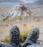 L'image de portrait du voyageur avec le trekking chausse le repos près du monastère principal Images stock