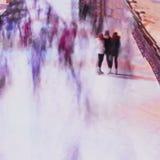 L'image de tache floue de trois amies sur des patins patinent contre le parc de ville de contexte, les gens, hiver, amitié, sport Images stock