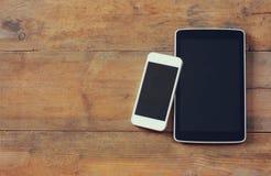 L'image de vue supérieure du dispositif de smartphone et de comprimé au-dessus de la pièce en bois de table pour le texte, prépar Images libres de droits
