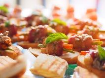 L'image des canapes délicieux, des casse-croûte de lard et des casse-croûte appétissants a placé sur la table Image libre de droits