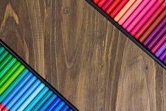L'image des crayons multicolores, deux a pêché des rangées, fond en bois Photo libre de droits