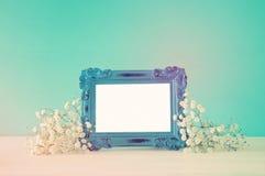 L'image du beau bouquet du ressort fleurit à côté du cadre vide de photo de vintage sur la table en bois Pour la moquerie de phot Images stock