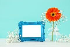 L'image du beau bouquet du ressort fleurit à côté du cadre vide de photo de vintage sur la table en bois Pour la moquerie de phot Image stock