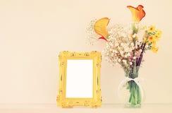 L'image du beau bouquet du ressort jaune fleurit à côté du cadre vide de photo de vintage au-dessus de la table blanche Pour la m Images stock