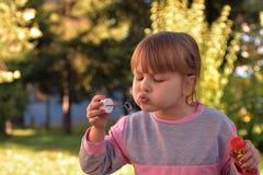 L'image du bulle d'air de soufflement de petite fille monte en ballon avec la vue des arbres et du parc verts à l'arrière-plan Images stock
