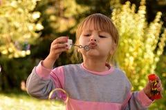 L'image du bulle d'air de soufflement de petite fille monte en ballon avec la vue des arbres et du parc verts à l'arrière-plan Photographie stock