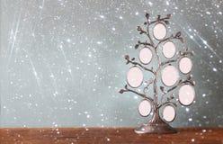 L'image du cadre classique d'antiquité de vintage de l'arbre généalogique sur la table en bois et le scintillement allume le fond Photographie stock