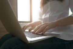 L'image en gros plan de la jeune femme remet dactylographier et écrire des massages Image libre de droits
