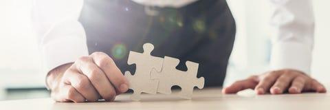 L'image large de vue d'un homme d'affaires tenant deux morceaux de puzzle s'assortissent photo stock
