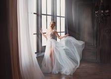 L'image magnifique du diplômé en 2019, fille dans la longue robe volante douce légère blanche avec la jambe nue seul se tient, cy photo stock