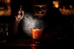 L'image obscurcie du barman verse un cocktail d'alcool utilisant le pulvérisateur photo stock