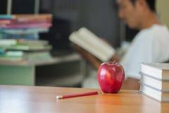 L'image orientée d'école comportant une pomme et une pile des livres le fond est un homme s'asseyant lisant un livre photographie stock libre de droits