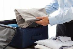 L'imballaggio dell'uomo d'affari copre nella borsa di viaggio Immagini Stock
