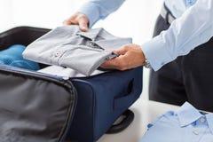 L'imballaggio dell'uomo d'affari copre nella borsa di viaggio Fotografia Stock Libera da Diritti