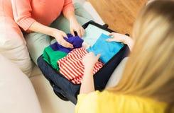 L'imballaggio della giovane donna copre nella borsa di viaggio Fotografia Stock Libera da Diritti