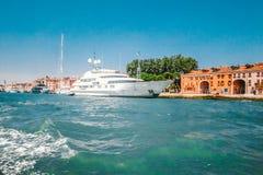 L'imbarcazione a motore ad alta velocità bianca ha attraccato lungo la costa su uno dei canali a Venezia, Italia Immagini Stock Libere da Diritti