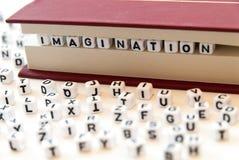 L'immaginazione di parola scritta con le lettere fra un libro impagina il fondo bianco con le lettere sparse intorno al concetto  immagine stock libera da diritti
