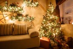 L'immagine calma del salone domestico moderno interno ha decorato l'albero di Natale ed i regali, il sofà, tavola coperta di cope Immagini Stock
