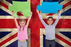L'immagine composita degli allievi elementari che tengono il puzzle collega Fotografia Stock