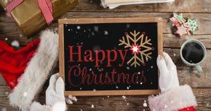 L'immagine composita del Babbo Natale che tiene un'ardesia con il Buon Natale manda un sms a Immagini Stock Libere da Diritti