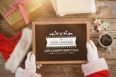 L'immagine composita del Babbo Natale che tiene un'ardesia con il Buon Natale manda un sms a Fotografia Stock Libera da Diritti