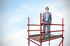 L'immagine composita dell'architetto attraente sorridente sulla tenuta del telefono progetta 3d Fotografia Stock