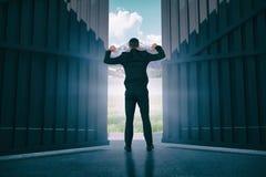 L'immagine composita dell'uomo d'affari che sta con le mani aumenta 3d Fotografie Stock