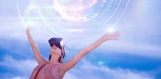 L'immagine composita della donna con le armi ha sollevato lo sguardo tramite il simulatore di realtà virtuale contro le sedere bi Fotografia Stock Libera da Diritti