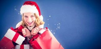 L'immagine composita della ragazza nella tenuta di modo dell'inverno presenta e sacchetti della spesa Fotografie Stock Libere da Diritti