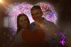 L'immagine composita delle coppie felici che tengono il grande cuore modella la carta Immagine Stock Libera da Diritti