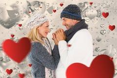 L'immagine composita delle coppie nell'inverno adatta l'abbraccio Fotografia Stock